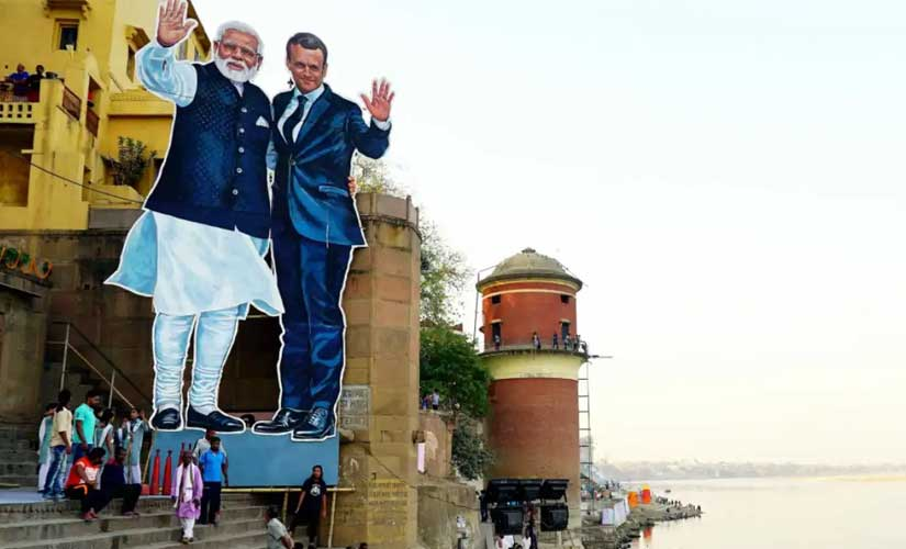 The giant cutout of Prime Minister Narendra Modi and French president Emmanuel Macron at Tulsi Ghat. PTI