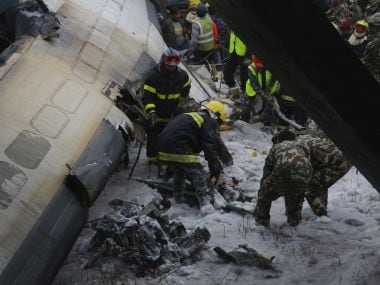 Nepalese rescuers work amid the debris after a passenger plane from Bangladesh crashed at the airport in Kathmandu. AP