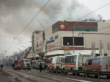 Smoke rises above a multi-story shopping center in the Siberian city of Kemerovo. AP