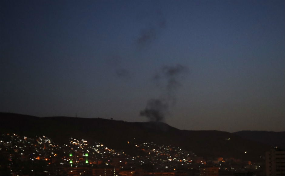 Smoke rising from east Damascus due to air strike. Syrian media reported that air defenses hit 13 rockets south of Damascus. After the attack ceased and the early morning skies went dark once more, vehicles with loudspeakers roamed the streets of Damascus blaring nationalist songs. AP