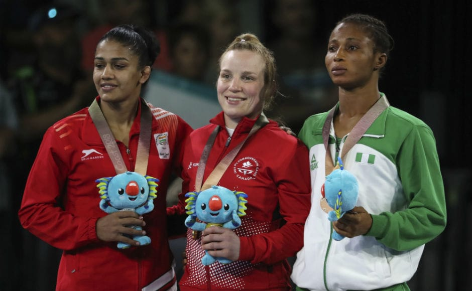 Canada's Gold medalist in women's FS 53Kg wrestling Dina Weicker, center, stands with India's Silver medalist Babita Kumari and Nigeria's Bronze medalist Bose Samuel during a medal ceremony. AP