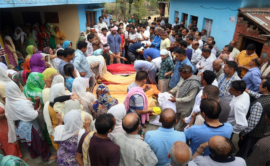 Relatives and family members gather around the bodies of the victims during a funeral in Khuwara village near Nurpur in Kangra district on Tuesday. PTI