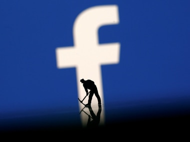 A figurine is seen in front of the Facebook logo. Image: Reuters