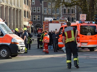 Rescue workers stand outside the area after the car crashed into the crowd. AP