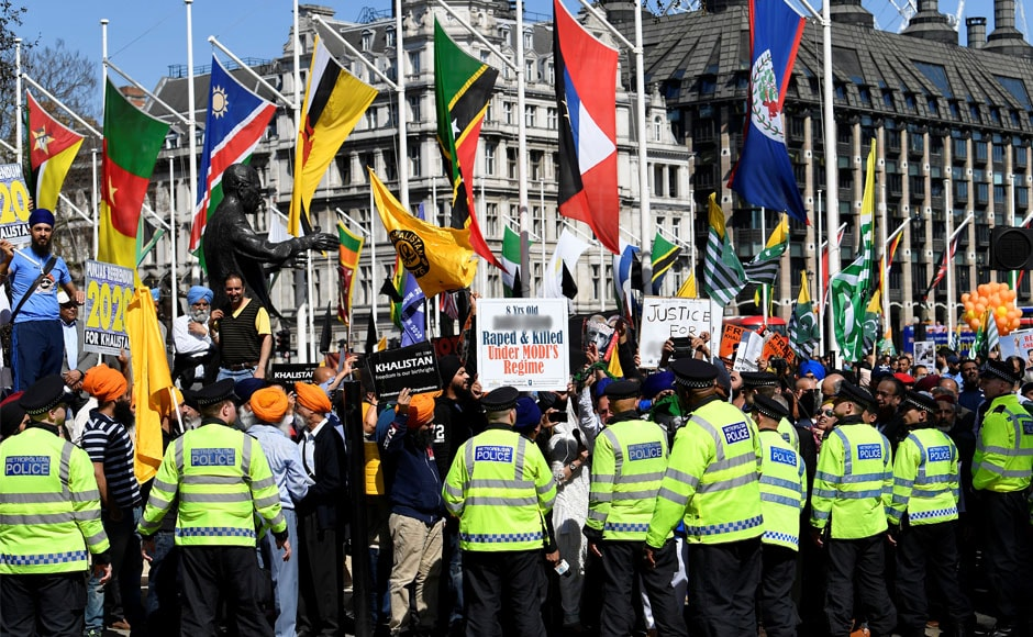 Police officers stand in front of demonstrators protesting against Modi in Parliament Square in London. Reuters