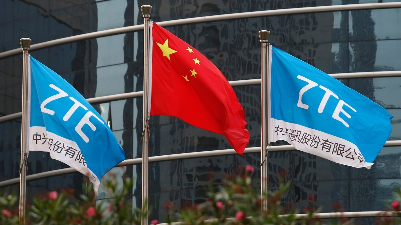 A Chinese national flag and two flags bearing the name of ZTE fly outside the ZTE R&D building in Shenzhen China