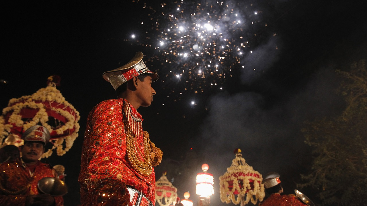 Members of the brass band play as fireworks are set off during a wedding procession in Noida on the outskirts of New Delhi December 11, 2012. The wedding season in India lasts for about four months and during wedding celebrations the bridegroom's family normally hires a brass band service to play at the wedding procession, in which the groom's family dances all the way to the wedding venue where the bride's family waits to receive them. The members of the band come together during wedding season to perform and earn around $10-12 per wedding. Picture taken December 11, 2012. REUTERS/Mansi Thapliyal (INDIA - Tags: SOCIETY BUSINESS EMPLOYMENT ENTERTAINMENT) ATTENTION EDITORS: PICTURE 19 OF 21 FOR PACKAGE 'INDIA'S WEDDING BANDS'. TO FIND ALL IMAGES SEARCH 'BRASS BAND' - GM1E8CL15ZK01
