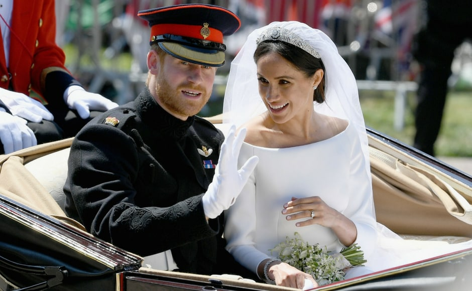 Prince Harry and his wife Meghan markle wave during their carriage procession after their wedding ceremony/Adrian Dennis/AFP