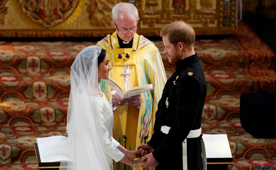 Prince Harry and Meghan Markle stand facing each other hand-in-hand before the Archbishop of Canterbury/Owen Humphreys/AFP