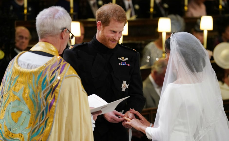 Meghan Markle and Prince Harry exchange rings during their wedding ceremony/Owen Humphreys/AFP