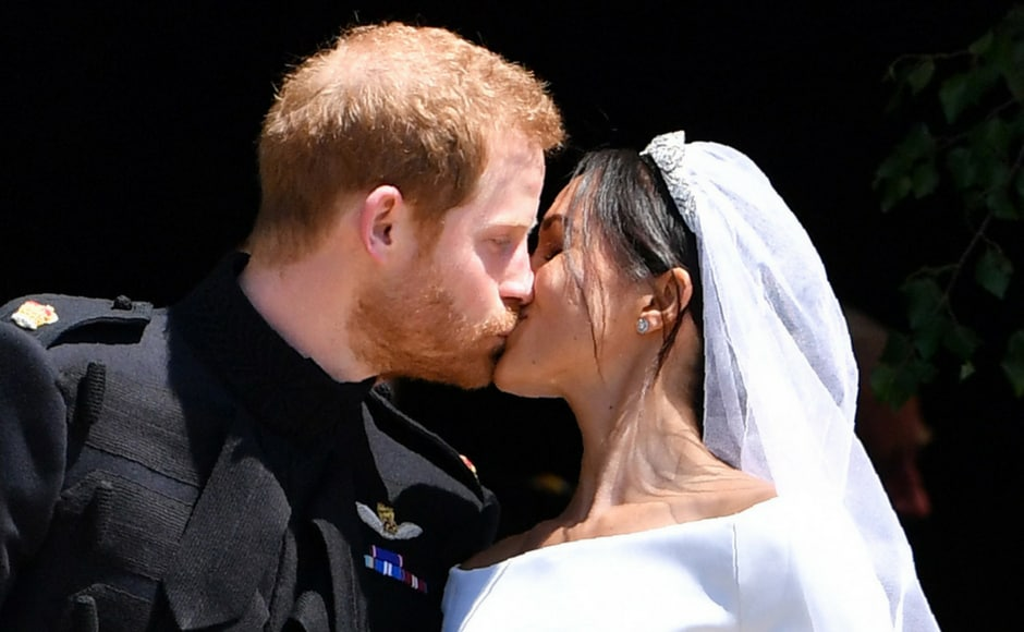 Prince Harry kisses his wife Meghan, Duchess of Sussex, as they leave from St George's Chapel after their wedding ceremony/Ben Stansall/AFP