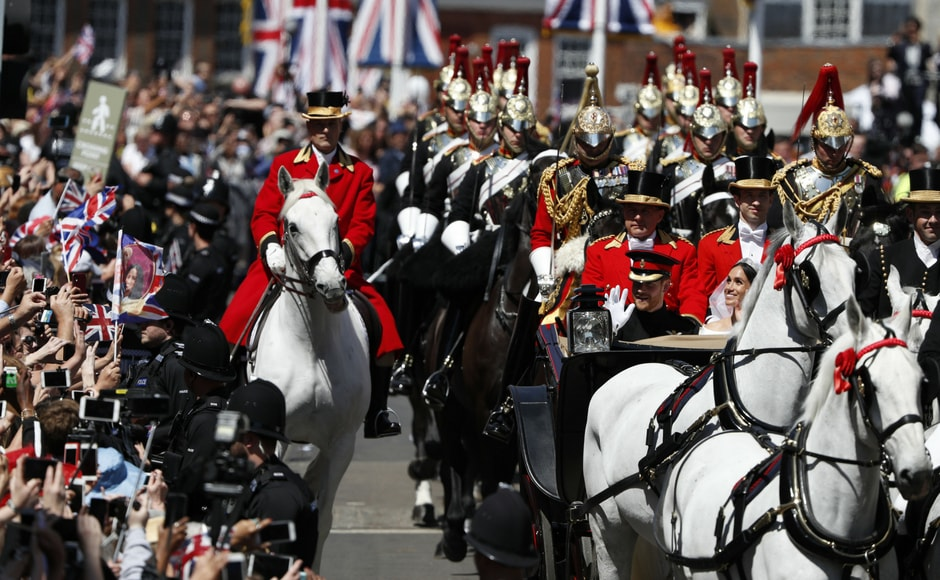 Prince Harry and his wife Meghan Markle wave during their carriage procession as they head back towards Windsor Castle/Adrian Dennis/AFP
