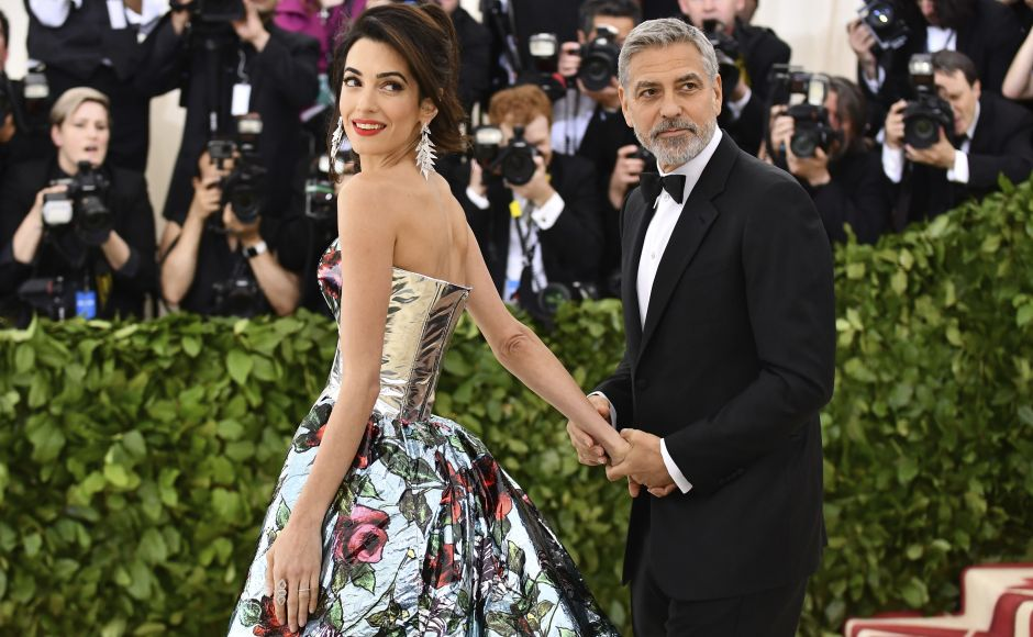 George Clooney (R) and his wife, Amal, were among the first to arrive at Monday's party. Amal was wearing a metallic Richard Quinn gown with train. Photo by Charles Sykes/Invision/AP