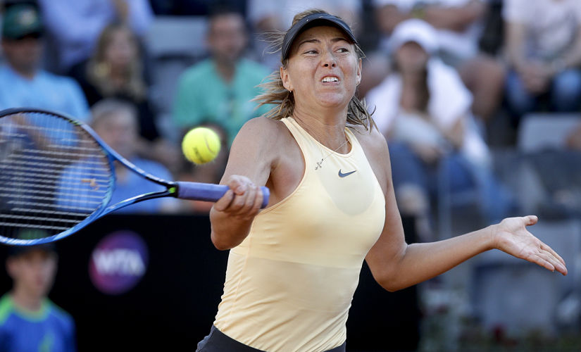 FILE - In this May 18, 2018, file photo, Russia's Maria Sharapova returns the ball to Latvia's Jelena Ostapenko, at the Italian Open tennis tournament in Rome. Sharapova will be competing in the French Open tennis tournament that begins on Sunday, May 27. (AP Photo/Andrew Medichini, File)