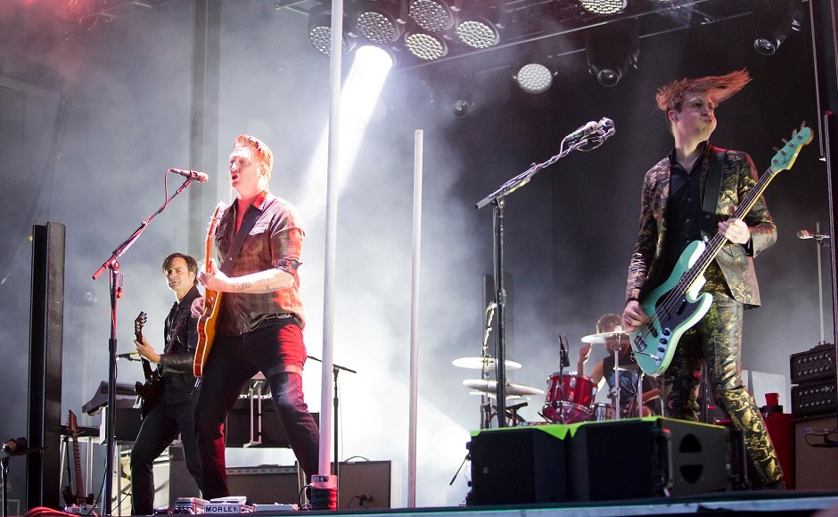 (From L-R) Troy Van Leeuwen, Josh Homme and Michael Shuman of Queens of the Stone Age perform at the Boston Calling Music Festival. Winslow Townson/Invision via AP