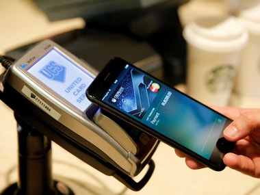 A man uses an iPhone 7 smartphone to demonstrate Apple Pay at a cafe. Image: Reuters