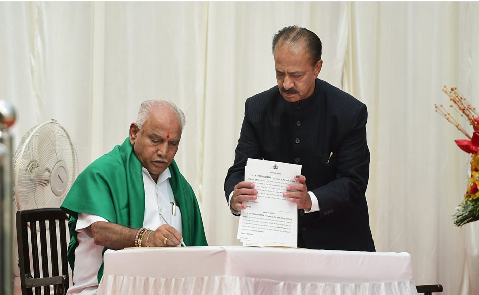 BS Yeddyurappa signs a register after being sworn-in as Chief Minister of Karnataka. Sporting a green shawl, symbolising solidarity with farmers in the state, the BJP leader took oath in the name of god and farmers. PTI