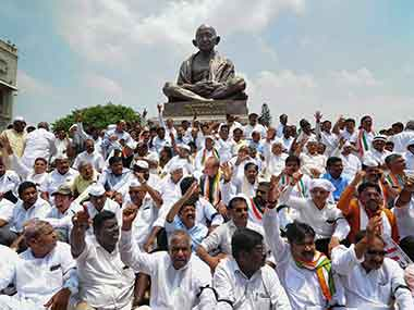 Congress party supporters and MLAs stage a dharna in front of the Gandhi Statue near Vidhan Soudha in Bengaluru to protest against the governor's invitation to BJP to form the state government. PTI