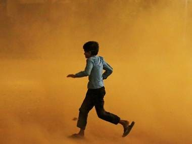 A boy runs for cover during a dust storm in New Delhi, India. Reuters