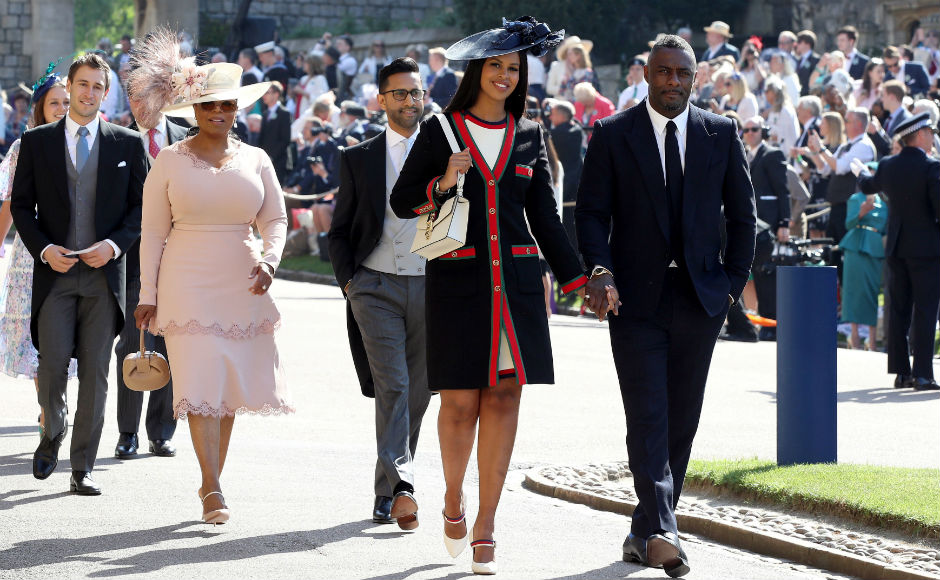 Idris Elba and Sabrina Dhowre followed by Oprah Winfrey arrive at St George's Chapel. Reuters