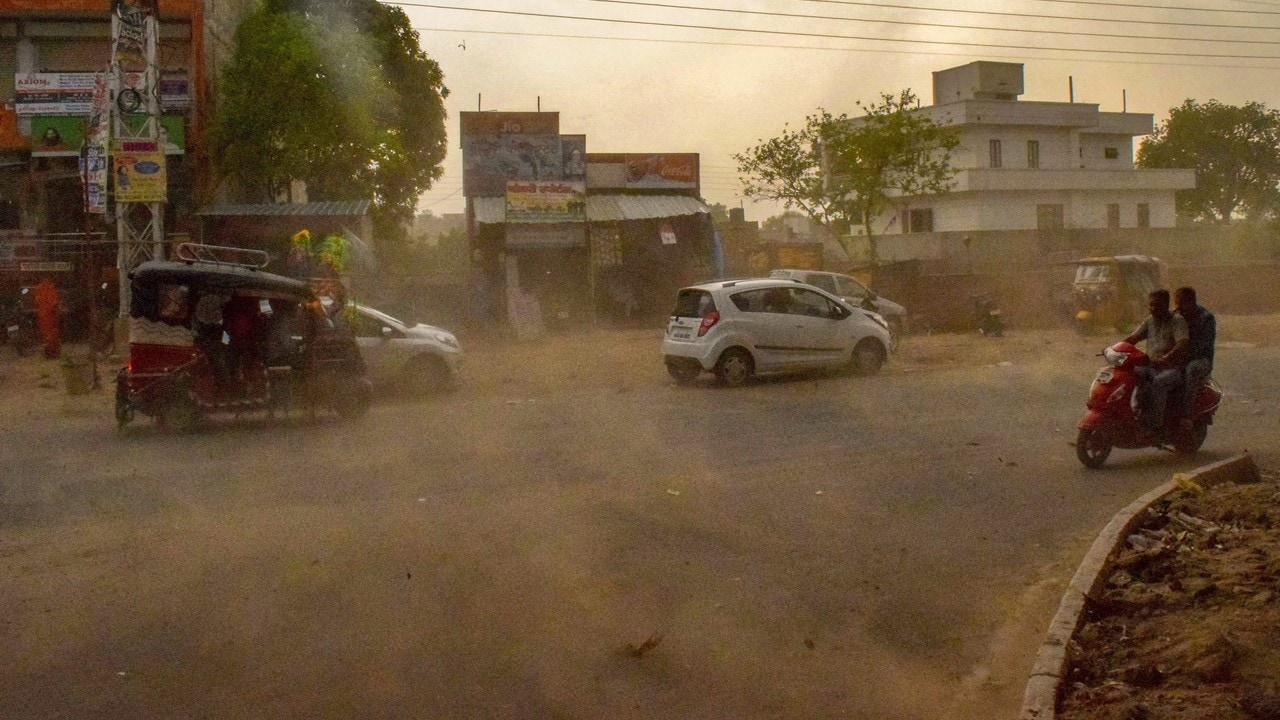 Vehicles ride past during a dust storm in Mathura on Wednesday. PTI