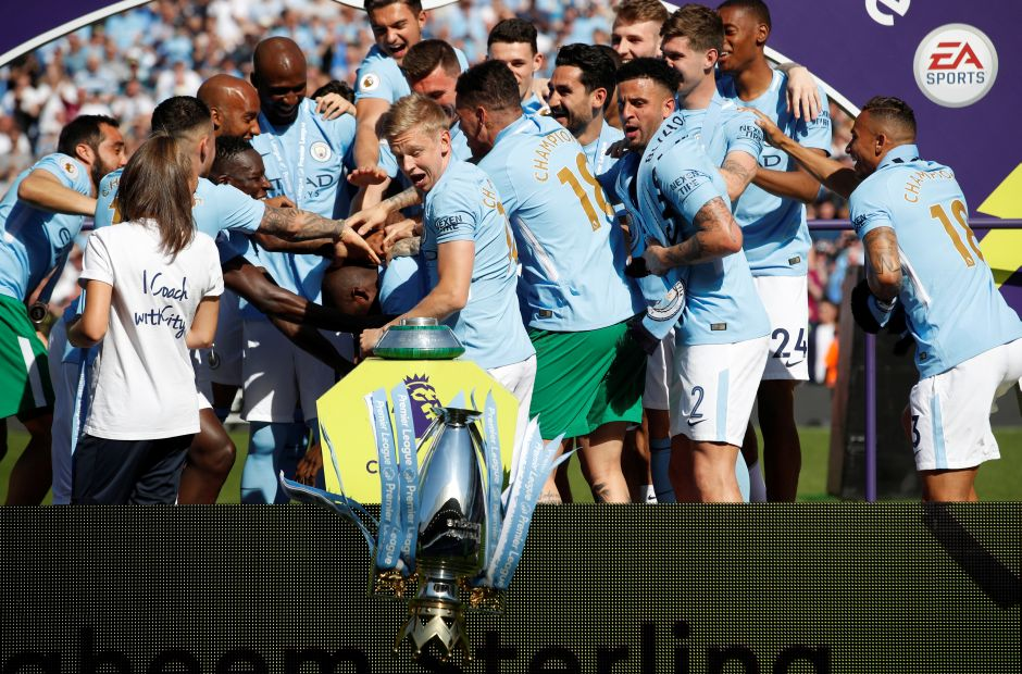 Manchester City's Oleksandr Zinchenko reacts as the trophy falls to the floor as players and staff celebrate. Yaya Toure was given the biggest cheer by fans as City's players walked up to the stage to collect the trophy. As many of them jumped on the midfielder, the trophy fell off its perch and onto the grass. Reuters