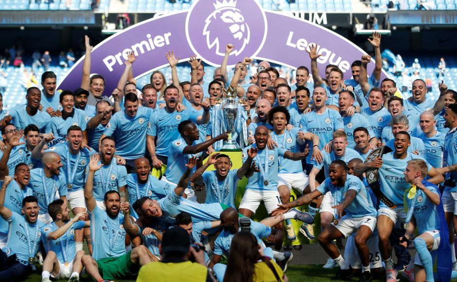 Manchester City players celebrate with the Premier League trophy. Blue-and-white tickertape flew up and fireworks exploded as Manchester City's players finally got their hands on the trophy on Sunday. Reuters