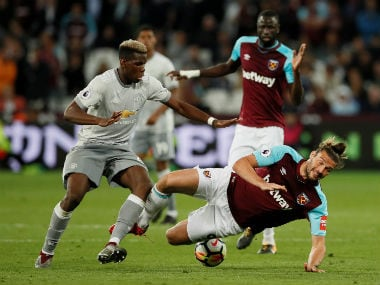 Manchester United's Paul Pogba in action with West Ham United's Andy Carroll. Reuters