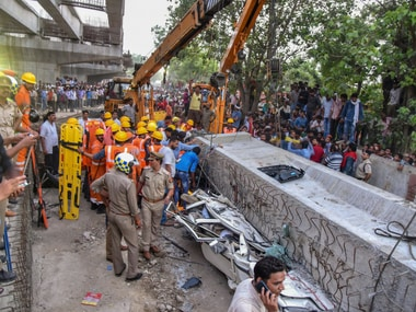 Locals and rescue teams gather near crushed vehicles after a portion of an under-construction flyover collapsed in Varanasi on Tuesday. PTI