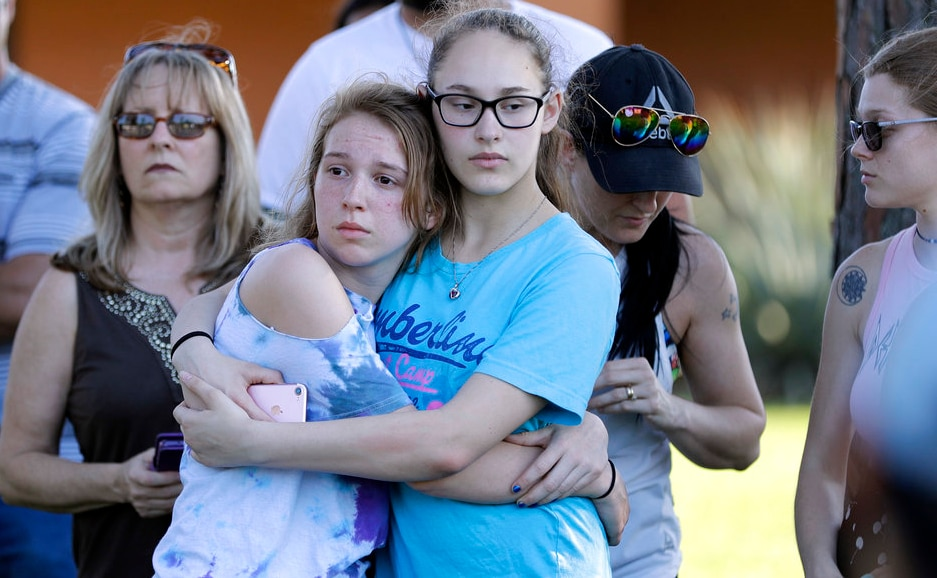 A Santa Fe High School freshman is comforted by her father during a prayer vigil following the high school shooting at Santa Fe, Texas, on Friday. AP