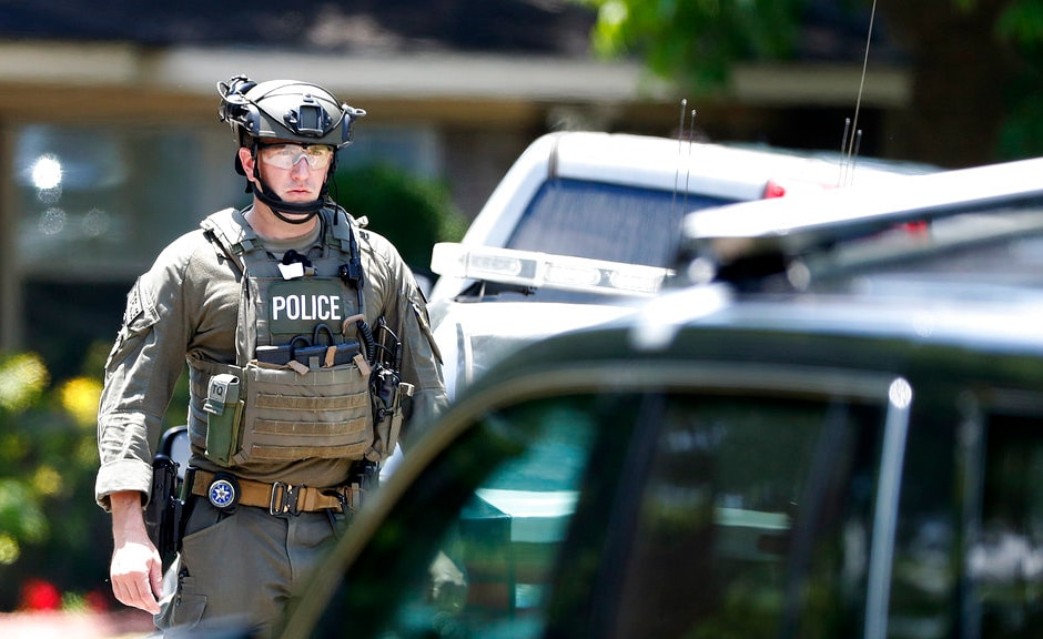 A state and federal law enforcement officeroutside a home in Alvin, Texas, as part of the investigation in the aftermath of the high school shooting. AP
