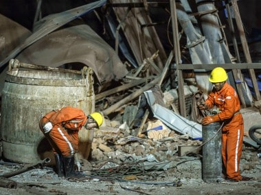 Rescuers working at the site of the explosion attempt to clear away the blast debris. AP