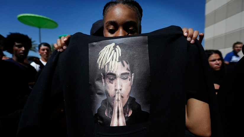Anneyah Lawson, 14, of St. Petersburg, Fla., holds up a sweatshirt with an image of slain rapper XXXTentacion, before his memorial on 27 June in Sunrise, Fla. Associated Press/Brynn Anderson