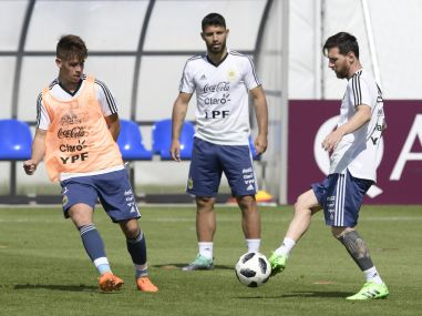 Argentina's Lionel Messi (R) passes the ball next to teammate forward Sergio Aguero (C) during a training session. AFP