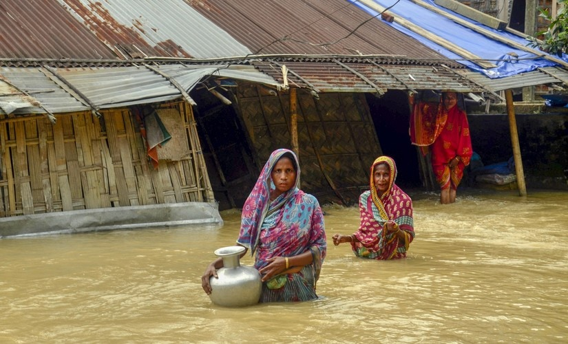 Villagers carry clean water as they wade across flood-affected areas at Nilambazar village, in Karimganj, Assam, on Sunday. PTI