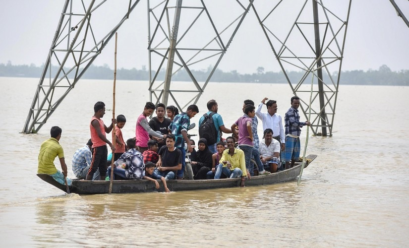 Villagers travel in a boat to cross across flood water, in Hojai, Assam, on Sunday.