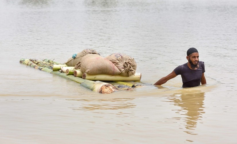 A villager transports his goods on a makeshift raft to cross across flood water, in Hojai, Assam, on Sunday. PTI