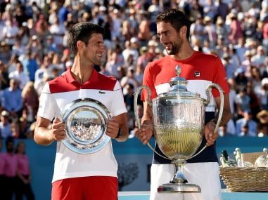 Marin Cilic (R) poses with the trophy after winning the final against Novak Djokovic. Reuters