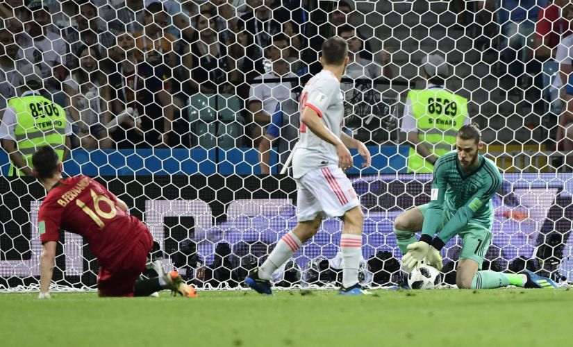 Spain's goalkeeper David De Gea (R) fails to block a second goal by Portugal's forward Cristiano Ronaldo (not in picture). AFP