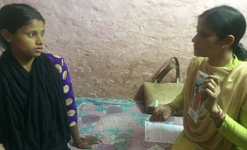Health supervisor Daya Pandey telling Sushma Paswan, 24, about mMitra service in the latter's home in West Delhi's Sagarpur area. mMitra is a free pre-recorded voice-message service that gives pregnant women information about taking care of themselves and their newborns. IndiaSpend