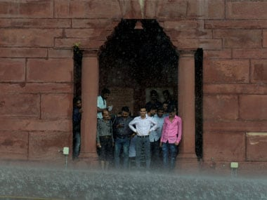 People take shelter under the arch of Raisina Hills during rainfall, in New Delhi . PTI