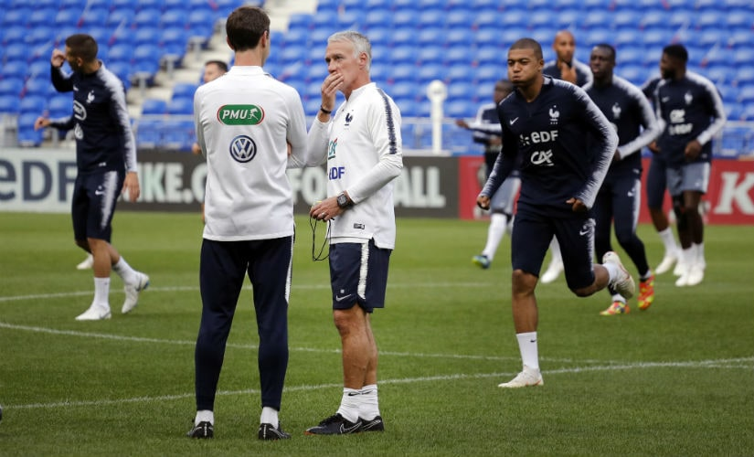 French national team head coach Didier Deschamps center speaks with his assistant during a team training session at the Groupama stadium in France. AP