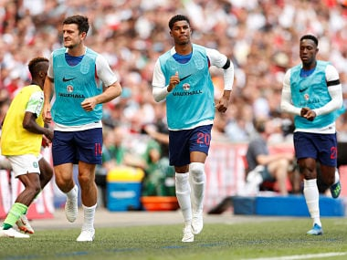 England's Harry Maguire and Marcus Rashford warm up on the sideline during a match. Reuters