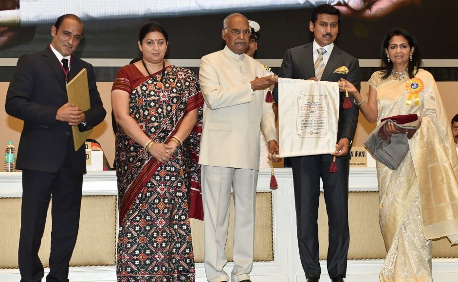 New Delhi: President Ram Nath Kovind confers Dadasaheb Phalke Award on veteran actor Vinod Khanna (posthumously), being received by his son Akshay Khanna and wife Kavita Khanna, during the 65th National Film Awards function at Vigyan Bhavan in New Delhi on Thursday. Union I&B Minister Smriti Irani and MoS for I & B Rajyavardhan Rathore are also seen. PTI Photo by Manvender Vashist (PTI5_3_2018_000140B) *** Local Caption ***