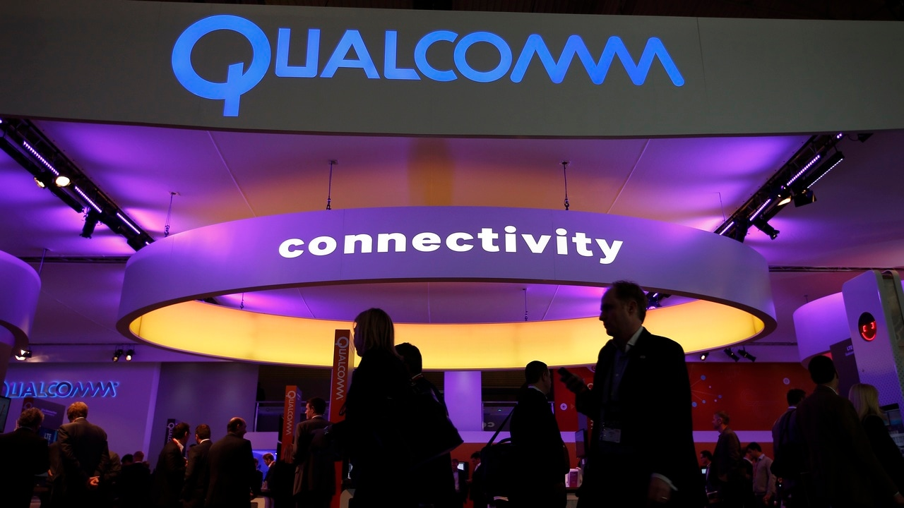 Visitors walk past the Qualcomm stand at the Mobile World Congress in Barcelona, February 24, 2014. The world's biggest mobile brands will jostle for the spotlight at the premier mobile industry event this week in Spain, but away from the glitzy displays chipmakers will be preoccupied with China, the largest mobile market on the planet. REUTERS/Albert Gea (SPAIN - Tags: BUSINESS TELECOMS) - GM1EA2O1FFY01