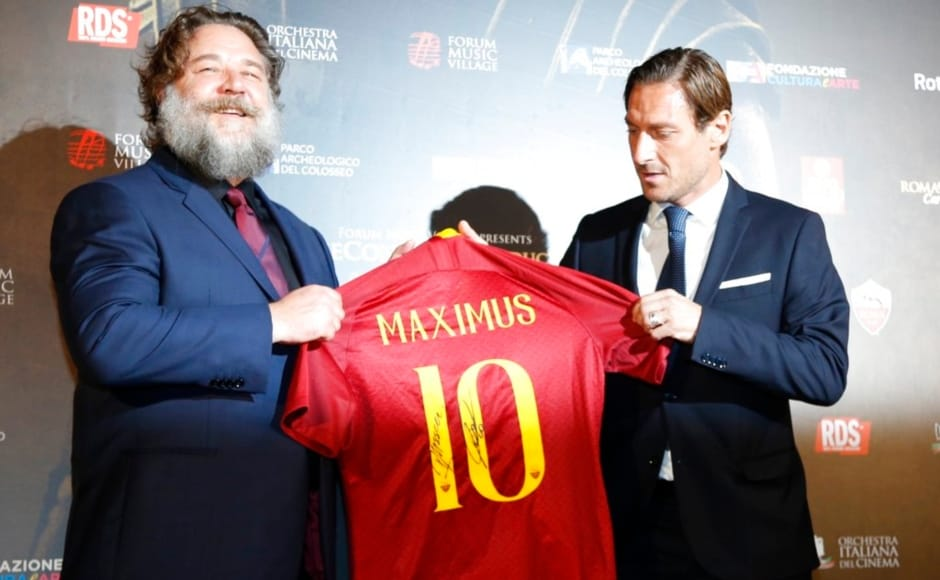 Russel Crowe (left) and former AS Roma player Francesco Totti hold up a soccer jersey with the name of Crowe's character in the Hollywood blockbuster and the number 10 which was Totti's number in his team as they pose on the red carpet of the screening. Image from AP/Domenico Stinellis
