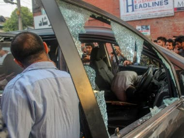 Police and locals inspect the damaged vehicle after suspected militants shot dead Shujaat Bukhari. PTI