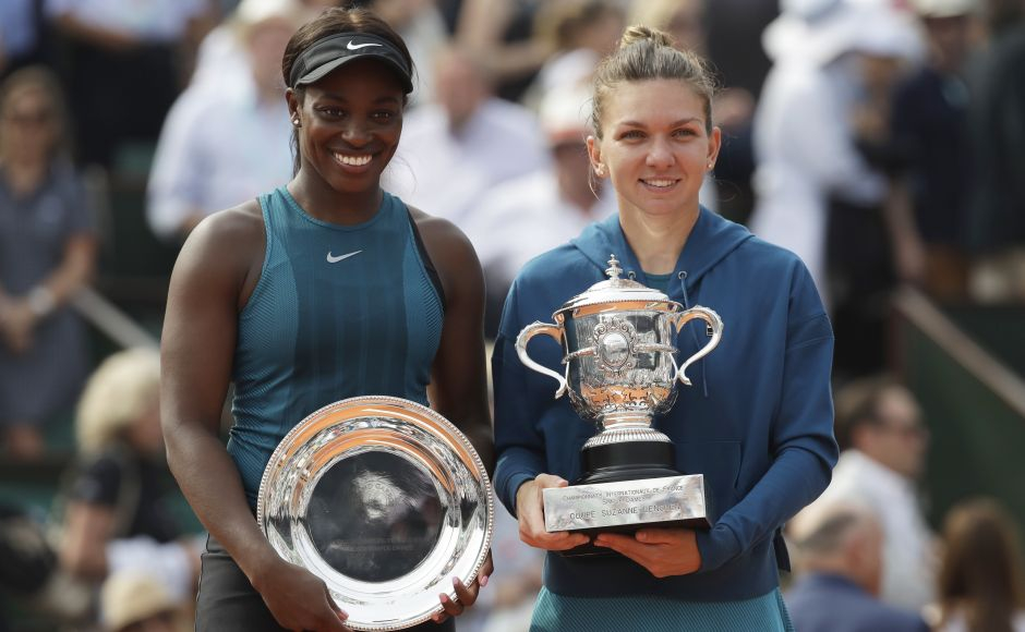 Romania's Simona Halep, right, holds the trophy as she poses with runner-up Sloane Stephens of the US after winning the final match of the French Open. Halep won in three sets 3-6, 6-4, 6-1, on Saturday. AP