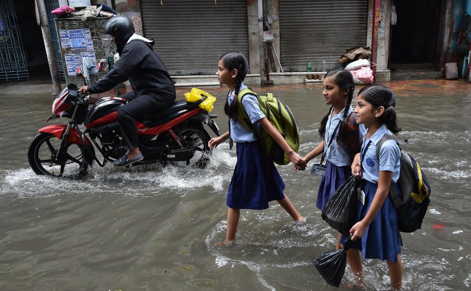 The state government's disaster management department sounded an alert to all the districts, an official at the secretariat said. School students wade through water in northern part of the city on Tuesday. PTI