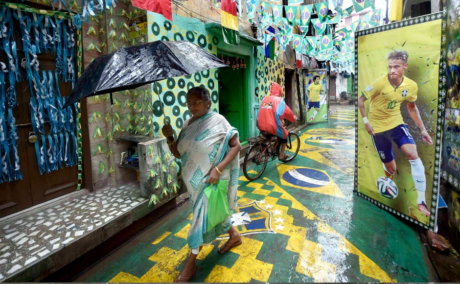 People commute on a road decorated by Brazil fans as FIFA World Cup 2018 fever grips the city, in Kolkata. PTI
